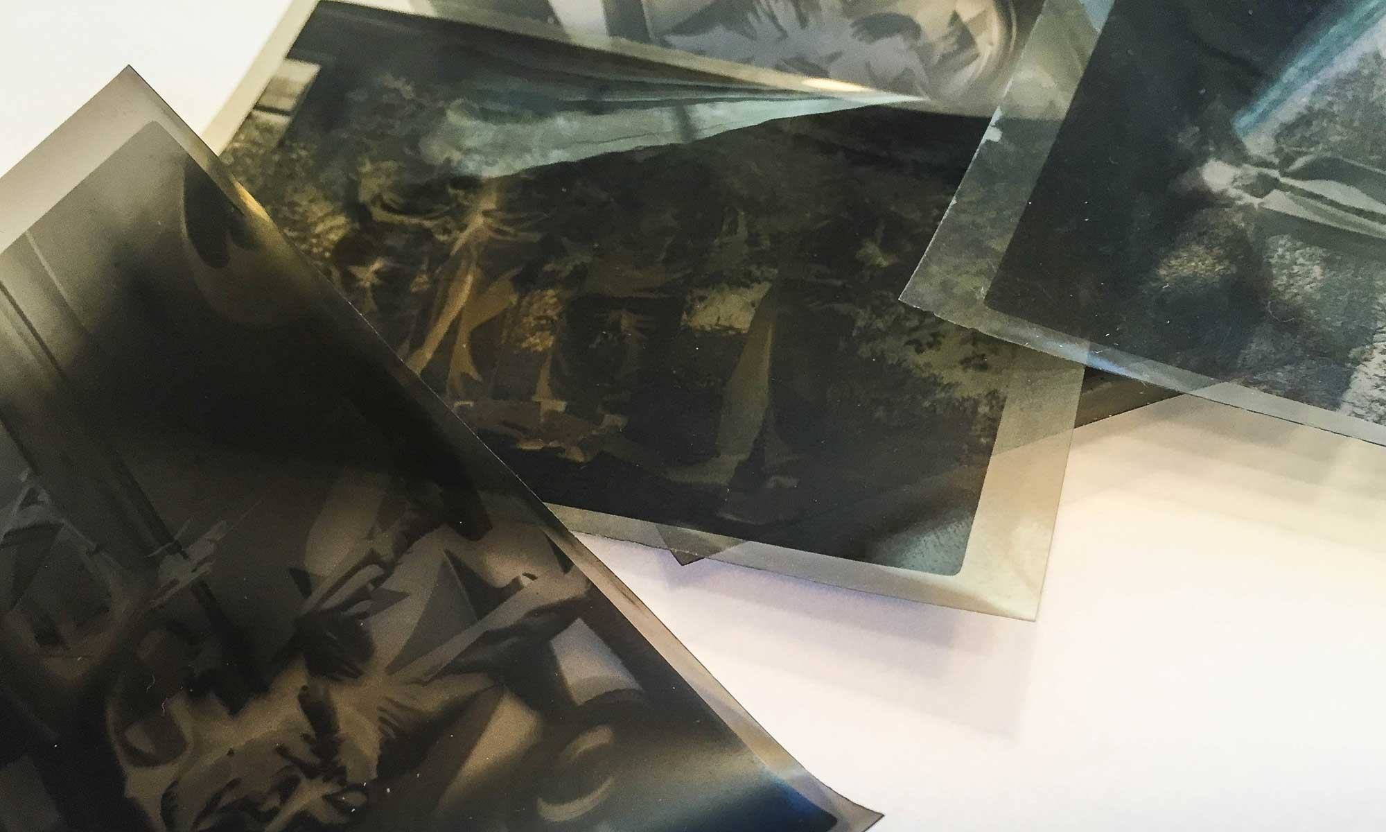 photo restoration-collection of black and white vintage negatives on table top